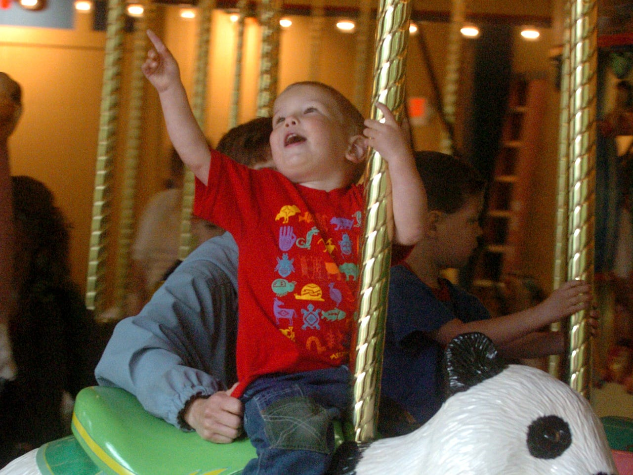 Nathan St. Peter, of Kalamazoo, checks out the lights as he rides the new Binda Conservation Carousel at Binder Park Zoo in 2007.
