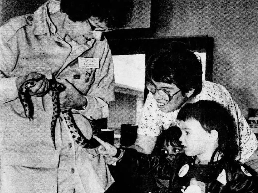 Nat Gesmundo, right, touches a fox snake held by Binder Park Zoo docent Rae Haas as zoo education specialist Carol Hill looks on in 1991.