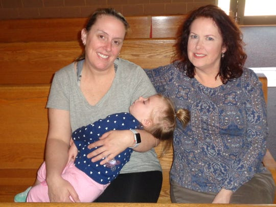 Jen Dube, left, and Beth Scordino take a break from their RCIA studies inside Our Lady of Good Counsel Church in Endicott. Dube is holding her 22-month-old daughter, Quinlynn.