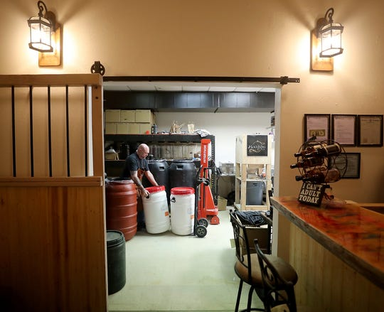 Tom Martin is framed in the tasting room doorway as he moves containers of mash at Black Ring Spirits in Port Orchard on Wednesday, April 10, 2019.