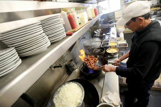 Sam Luong cooks up an order of sesame chicken in the kitchen at Emperor's Palace in Bremerton on Thursday, April 11, 2019.
