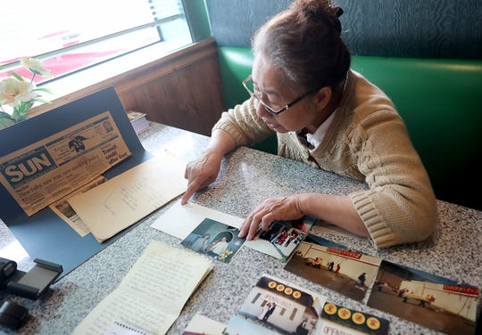 Nu Kim Tang looks over photos and letters at Emperor's Palace in Bremerton on Thursday, April 11, 2019.