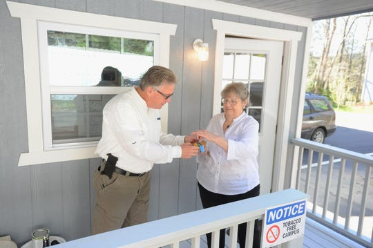 Nancy Blevens, the resident manager at Hope for Tomorrow, hands a set of keys to Swannanoa Valley Christian Ministry homeless outreach coordinator Sonny Moore outside of the community's resource center.