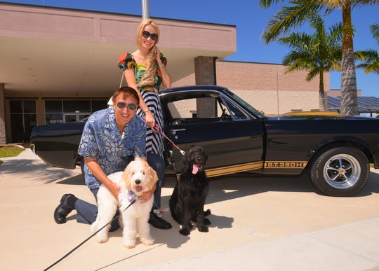 Mark and Tetiana Pieloch pose with Marlowe, a white goldendoodle, and Ziggy, a black Labradoodle, in front of a 1966 Ford Mustang Shelby GT350H at the American Muscle Car Museum in Melbourne.