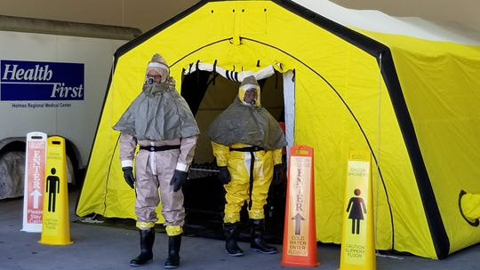 """Emergency personnel in biohazard suits  at Health First wait for """"victims"""" of a simulated chemical attack in a disaster training drill in Brevard County April 11, 2019."""