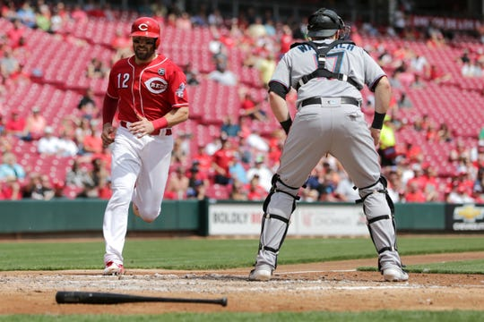 Cincinnati Reds catcher Curt Casali (12) scores on an RBI single by Cincinnati Reds first baseman Joey Votto (19) (not pictured) in the fifth inning of an MLB baseball game against the Miami Marlins, Thursday, April 11, 2019, at Great American Ball Park in Cincinnati.