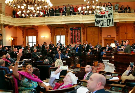 "Some members of the Ohio House applaud following their vote while others photograph protestors who unfurled banners reading ""This is not a House of Worship"" and ""This is not a Doctor's office"" following a vote on the Heartbeat Bill at the Ohio Statehouse in Columbus, Ohio on Wednesday, April 10, 2019. The House members voted in the controversial ""Heartbeat Bill"" that bans abortion at the first sounds of a fetal heartbeat, which is around 6 weeks after conception. Many protestors shouted in the hallway outside of the meeting where House members decided to pass the bill. (Brooke LaValley/The Columbus Dispatch via AP)"