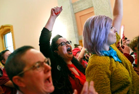 "Kimberly Inez McGuire shouts ""shame"" while members of the Ohio House of Representatives exit the chamber after passing a bill that would ban abortion at the first sounds of a fetal heartbeat, which can happen as early as six weeks into a woman's pregnancy."