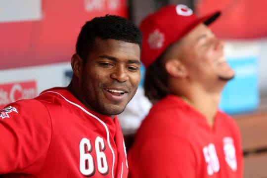 Cincinnati Reds right fielder Yasiel Puig (66), left, shares a laugh with Cincinnati Reds starting pitcher Luis Castillo (58) in the dugout in the second inning of an MLB baseball game against the Miami Marlins, Thursday, April 11, 2019, at Great American Ball Park in Cincinnati.