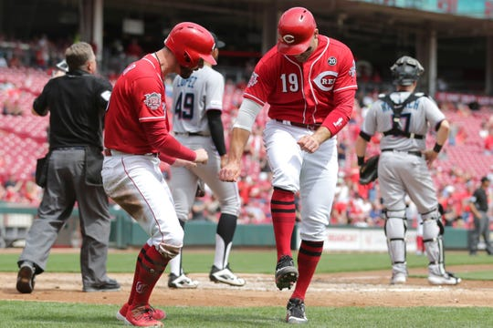 Cincinnati Reds right fielder Jesse Winker (33), left, and Cincinnati Reds first baseman Joey Votto (19), right, celebrate scoring on a double by Cincinnati Reds right fielder Yasiel Puig (66) in the fifth inning of an MLB baseball game against the Miami Marlins, Thursday, April 11, 2019, at Great American Ball Park in Cincinnati.