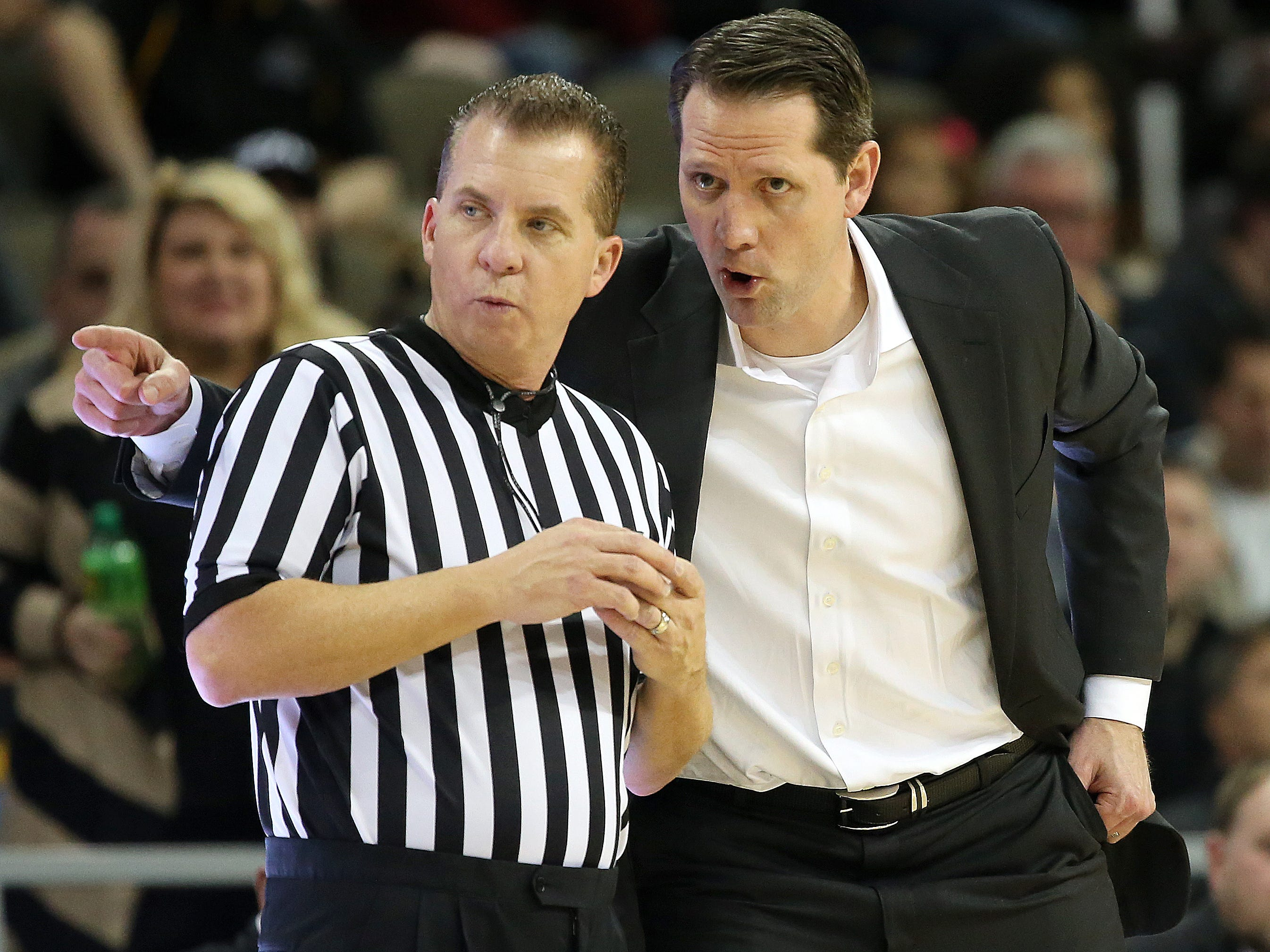 Northern Kentucky Norse head coach John Brannen, right, talks to an official in the first half during the NCAA college basketball game between Oakland Golden Grizzlies and the Northern Kentucky Norse, Friday, Jan. 26, 2018, at BB&T Arena in Highland Heights, Kentucky.