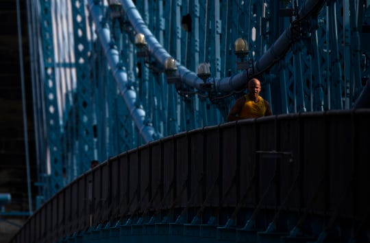 A man runs across the Roebling Bridge on Wednesday, April 10, 2019, in Cincinnati.