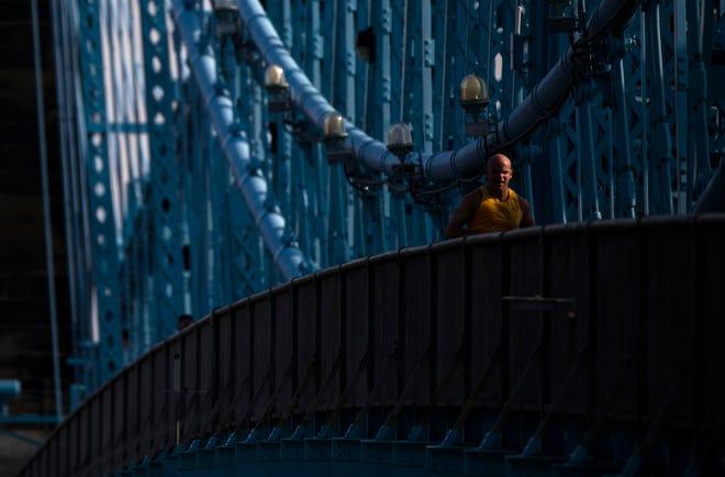 A man runs across the Roebling Bridge on Wednesday, April 10, 2019, in Cincinnati.