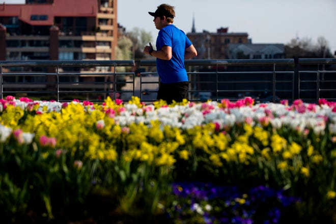 A man runs along Smale Riverfront Park on Wednesday, April 10, 2019, in Cincinnati.