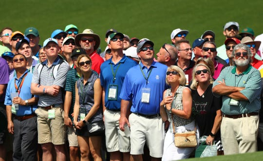 Patrons in the gallery watch a chip shot by Rickie Fowler (not pictured) on the 2nd hole during the first round of The Masters golf tournament at Augusta National Golf Club.