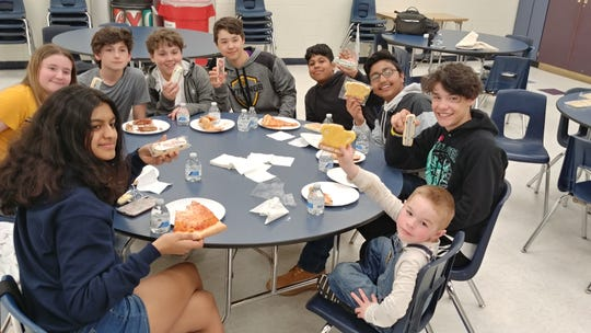 A group of South Brunswick middle school students enjoy pizza provided by the  police department for showing kindness and compassion to a 5-year-old boy at the town skate park.