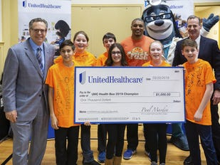 Mark Elsasser, CEO, Westfield Area YMCA (far left), Paul Marden, CEO, UnitedHealthcare of New Jersey (far right) and UnitedHealthcare's mascot Dr. Health E Hound celebrate with a team of seventh graders from Orange Avenue School who won the 2019 UnitedHealthcare Health Bee in overtime at the Westfield YMCA.. UnitedHealthcare awarded Orange Avenue School funding for its health and wellness programs with a $1,000 grand prize.