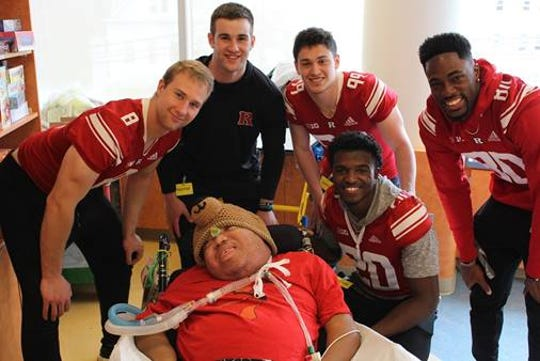 Rutgers football players Artur Sitkowski, Cooper Heisey, patient Poppy, Gavin Haggerty, Avery Young, and Monterio Hunt at Children's Specialized Hospital — New Brunswick.