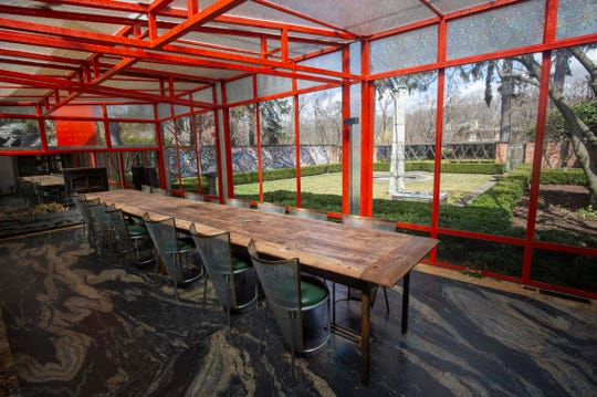 The newer dining room designed by architect William Massie has  glass  walls framed with Chinese red metal. It's heated and cooled and has a fireplace. A garage-door mechanism lets the glass walls be raised whenever it's pleasant out, so the dining is outdoors.