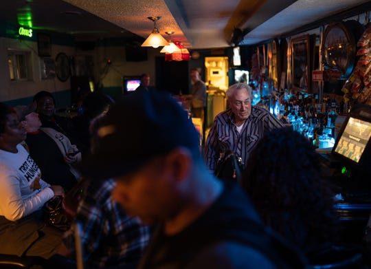 Hec's Bar owner Bob Van Maele, 76, tends the bar on a busy Friday night, surrounded by regulars.