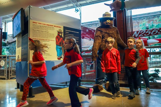 Children stop to take a photo with Smokey Bear at the Michigan Outdoor Center in Detroit on Thursday, April 11, 2019.  Smokey Bear informs people about the danger of wildfires and is celebrating his 75th anniversary by going digital.