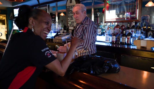 "Debra Ollis of Warren laughs after Hec's Bar owner Bob Van Maele pours her a foamy beer on Friday, March 29, 2019. ""I'm like Bob's daughter,"" Ollis said. ""I love him so much, I really do. He aggravates the hell out of me, but I love him."""