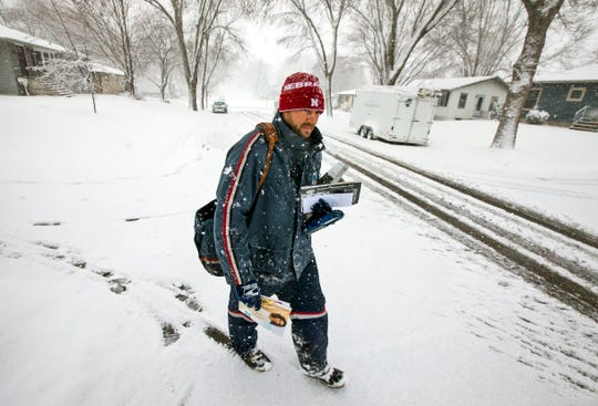 Postal Service carrier Chad Jacobs delivers mail  Wednesday, April 10, 2019, in Rochester, Minn. Jacobs said he doesn't mind cold and prefers it over hot days.