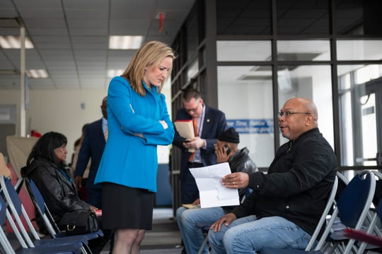 Secretary of State Jocelyn Benson chats with Frank McGhee, of Detroit, at the SOS branch office at Cadillac Place, in Detroit, April 11, 2019.  Benson announced plans to improve wait times and services at SOS branches across the state.