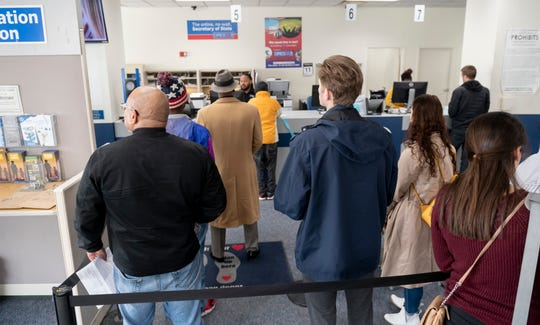 "Customers wait in line at the Secretary of State branch office at Cadillac Place, in Detroit, Thursday. April 11, 2019. ""Our current system is inconsistent, outdated and inefficient,"" summarized Secretary of State Benson."""
