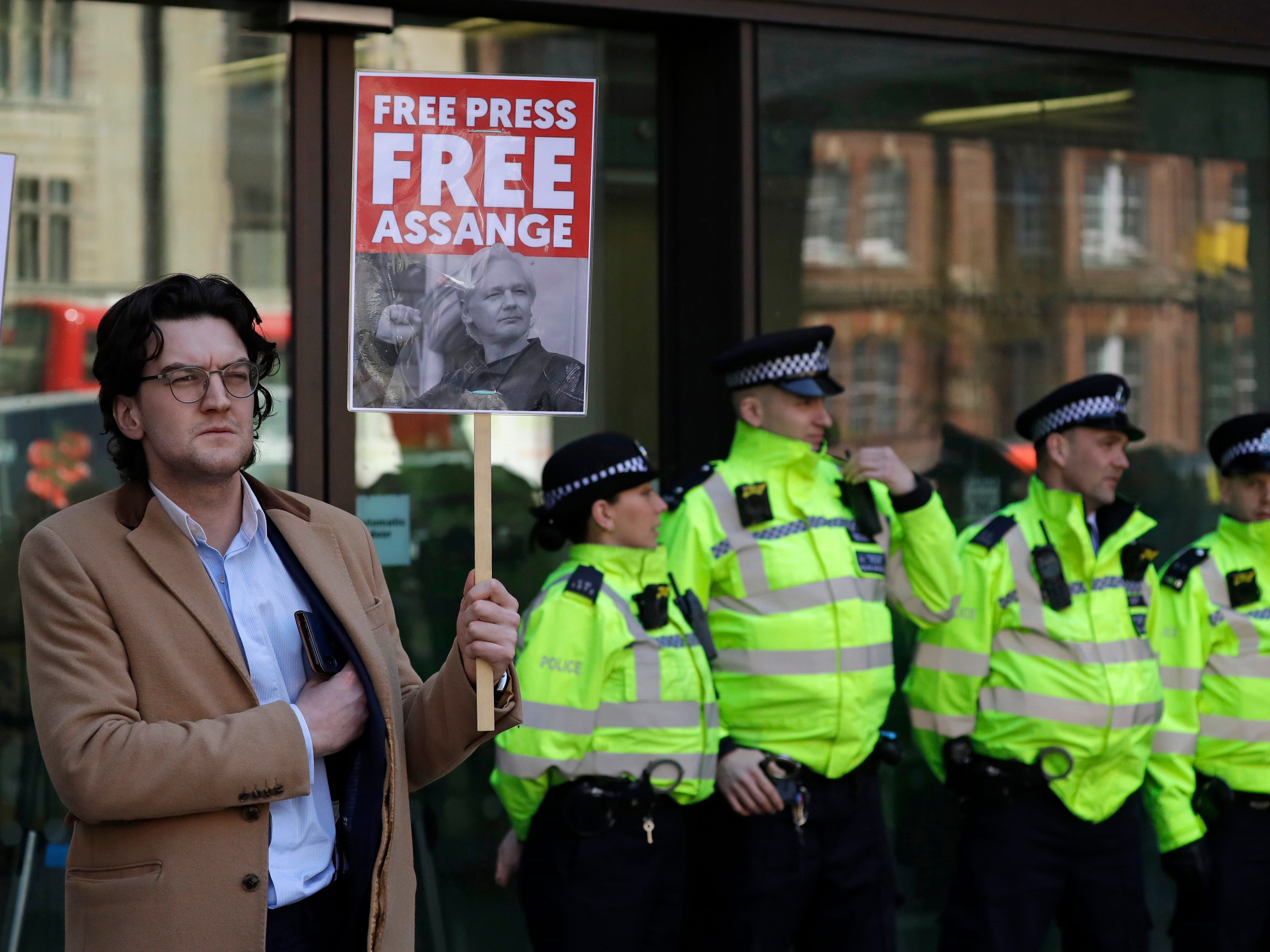 A protester demonstrating in support of WikiLeaks founder Julian Assange holds a placard outside Westminster magistrates court where he was appearing in London, Thursday, April 11, 2019. Police in London arrested WikiLeaks founder Assange at the Ecuadorean embassy Thursday, April 11, 2019 for failing to surrender to the court in 2012, shortly after the South American nation revoked his asylum.