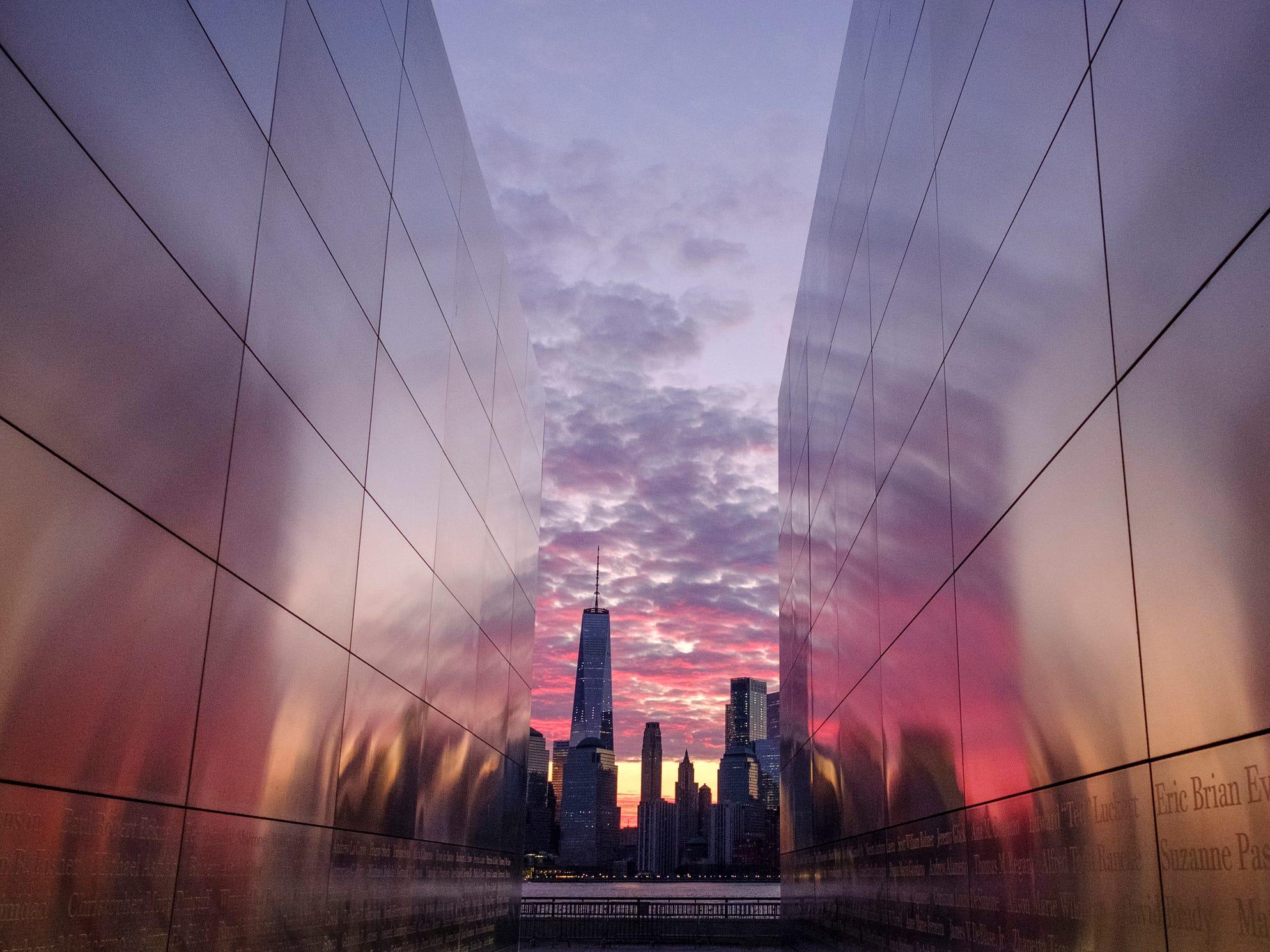 Framed through the Empty Sky Memorial in Jersey City, N.J., sunrise lights up the sky behind the New York City skyline Thursday, April 11, 2019.