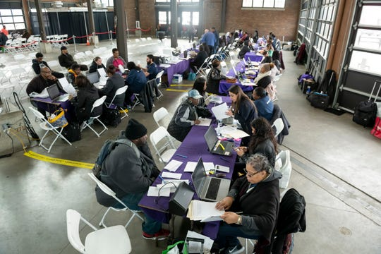 Wayne County residents sit down with customer service representatives during a customer assistance day at Eastern Market Shed 3, in Detroit, April 10, 2019.