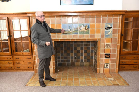 Southfield Mayor Ken Siver, also board  president of the Southfield Nonprofit Housing Corporation, shows a beautiful tiled fireplace in the former Academy of Southfield, built in 1929.  The SNHC is looking for funding to convert it to senior housing.
