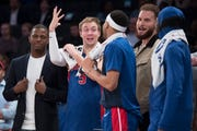 Detroit Pistons guard Luke Kennard (5) celebrates with teammates at the bench in the final seconds of the game.