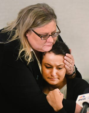 Attorney Karen Truszkowsk holds her client, Michigan State University student Bailey Kowalski, 22, during an press conference in East Lansing Thursday concerning an alleged sexual assault by three MSU basketball players.