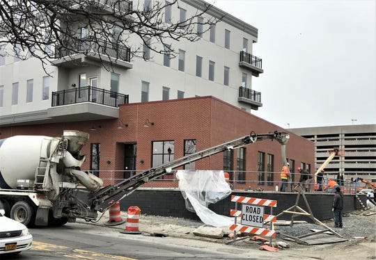 Construction workers pour concrete Thursday morning on the east end of a new four-story building at 100 W. Water St. in Elmira.