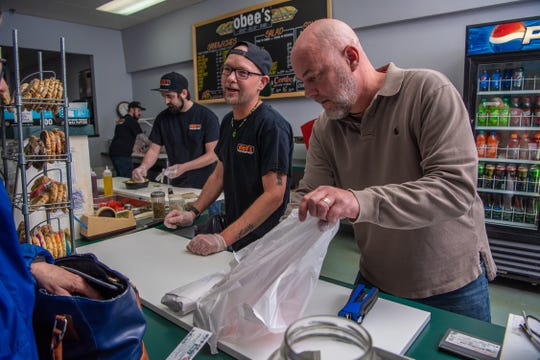 Jeremy Block, co-owner of Obee's, bags a customer's lunch on Wednesday, April 10, 2019, in Fort Collins, Colo.  Block recently purchased the sandwich shop from Lou Jerome, who owned the business for 17 years.