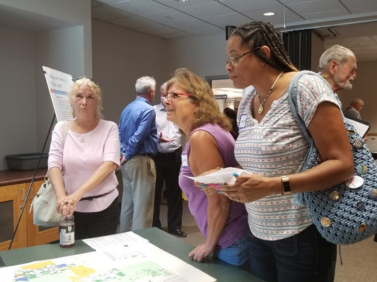 Lee County resident Monica Walzz, right, examines map of mine locations in Lee County at workshop meeting on mine rule changes,