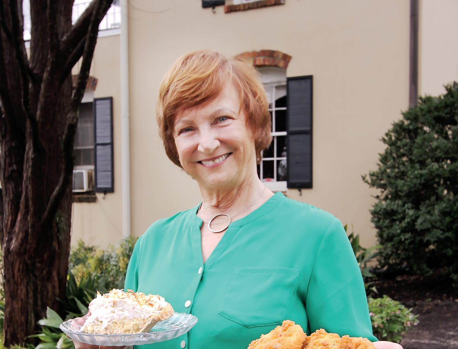 Mary Jones holds a plate of fried green tomatoes and a slice of coconut creme pie at Mary's at Falls Cottage.
