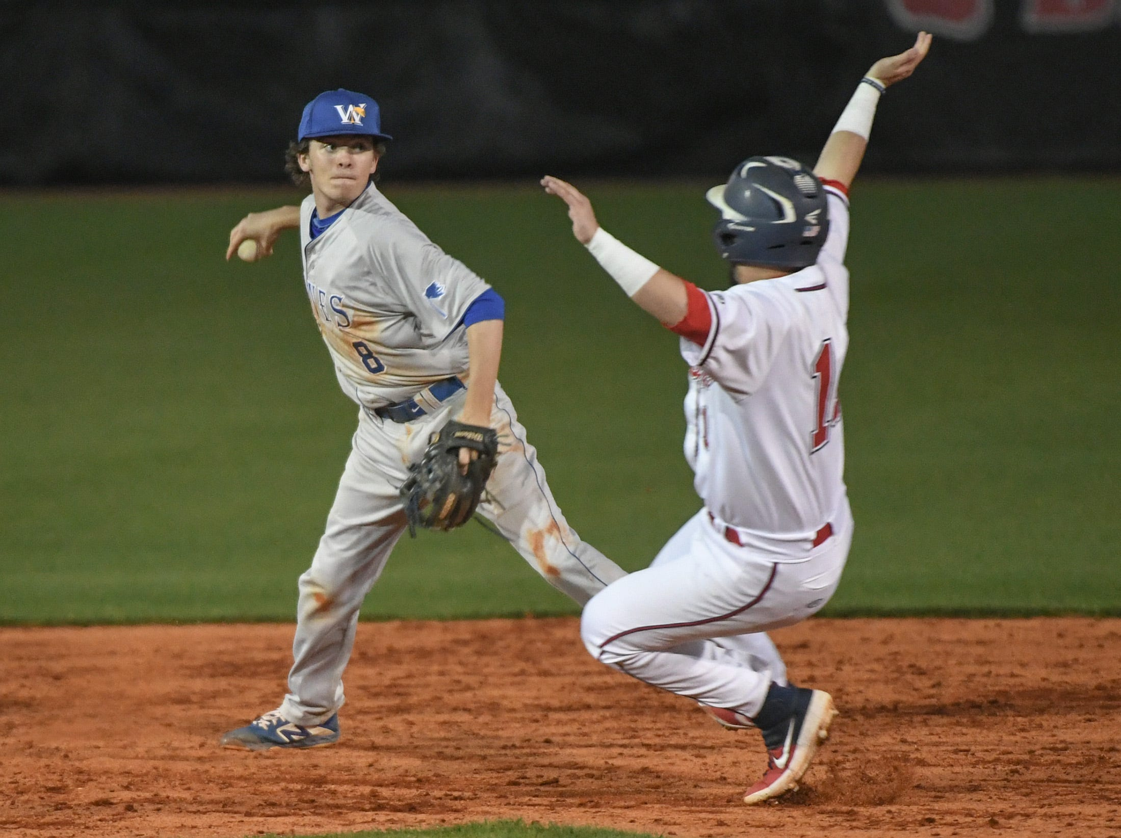 Wren shortstop Cam Williams (8) turns a double play over Belton-Honea Path senior Braden Galloway (11) during the bottom of the sixth inning at Belton-Honea Path High School in Honea Path Wednesday, April 10, 2019.