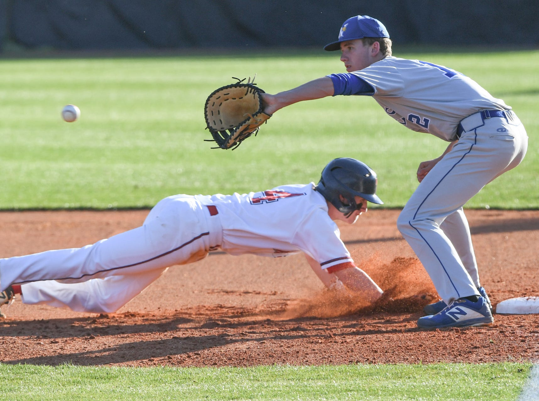 Belton-Honea Path sophomore Talmadge Lecroy (4) dives safely back to first under the tag of Wren first baseman Cooper Thomas (12) during the bottom of the first inning at Belton-Honea Path High School in Honea Path Wednesday, April 10, 2019.
