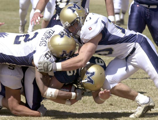 Kane Ioane (right) and Joey Thomas of Montana State converge on receiver Bryan Molen during the Bobcats' Blue-Gold scrimmage in Fort Benton in April of 2002.