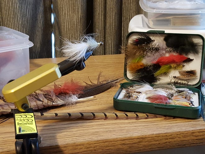A fly-tying work area can be as simple as an old table to hold a vice and plastic tubs.