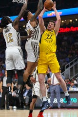 Apr 10, 2019; Atlanta, GA, USA; Indiana Pacers forward T.J. Leaf (22) shoots past Atlanta Hawks forward John Collins (20) and forward Taurean Prince (12) in the first quarter at State Farm Arena.