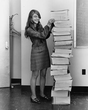 Margaret Hamilton in 1969, standing next to listings of the software she and her MIT team produced for the Apollo project.