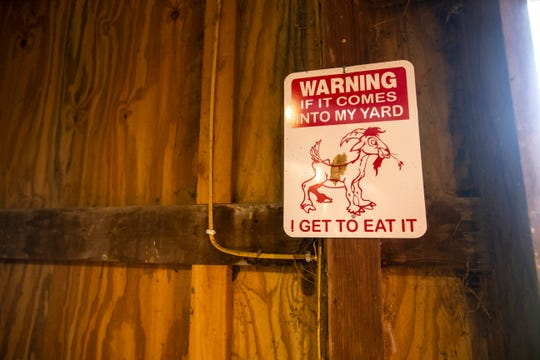 A 'warning' sign hangs on the wall of a building housing dairy goats on Thursday, April 11, 2019, at Lucky Star Farm in Iowa City, Iowa.