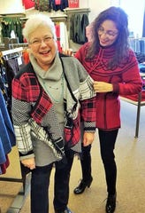 Williamsburg area resident Renee Driscoll tried on a flyaway cardigan at an area store last November under the watchful eye of Susi Norman of Kalona, an entrepreneur who counsels women on their wardrobes and more.