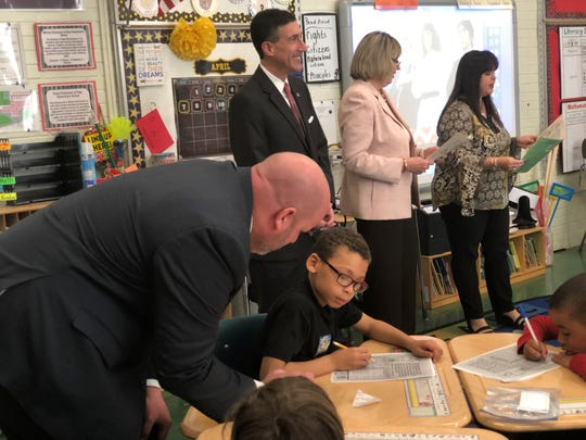 Ed Jackson III, the regional director for U.S. Rep. David Kustoff, helps students as they map out their short-term and long-term savings goals. The congressman and Commercial Bank representatives gave examples of what those goals may be.