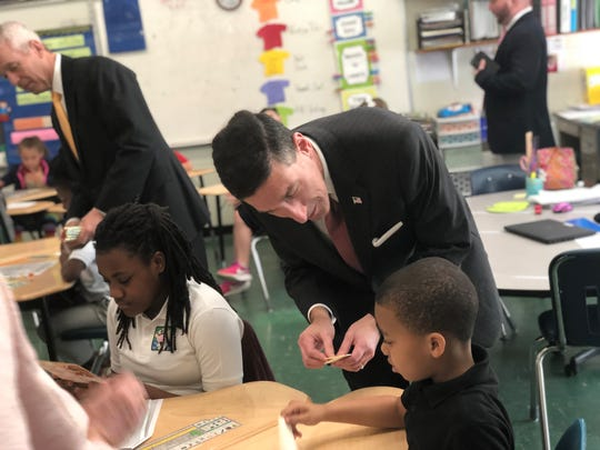 U.S. Rep. David Kustoff passes out his business cards to Pope Elementary second graders after he and Commercial Bank representatives gave a lesson on financial literacy Thursday. After the presentation, he invited the students to Washington, D.C., for a tour.