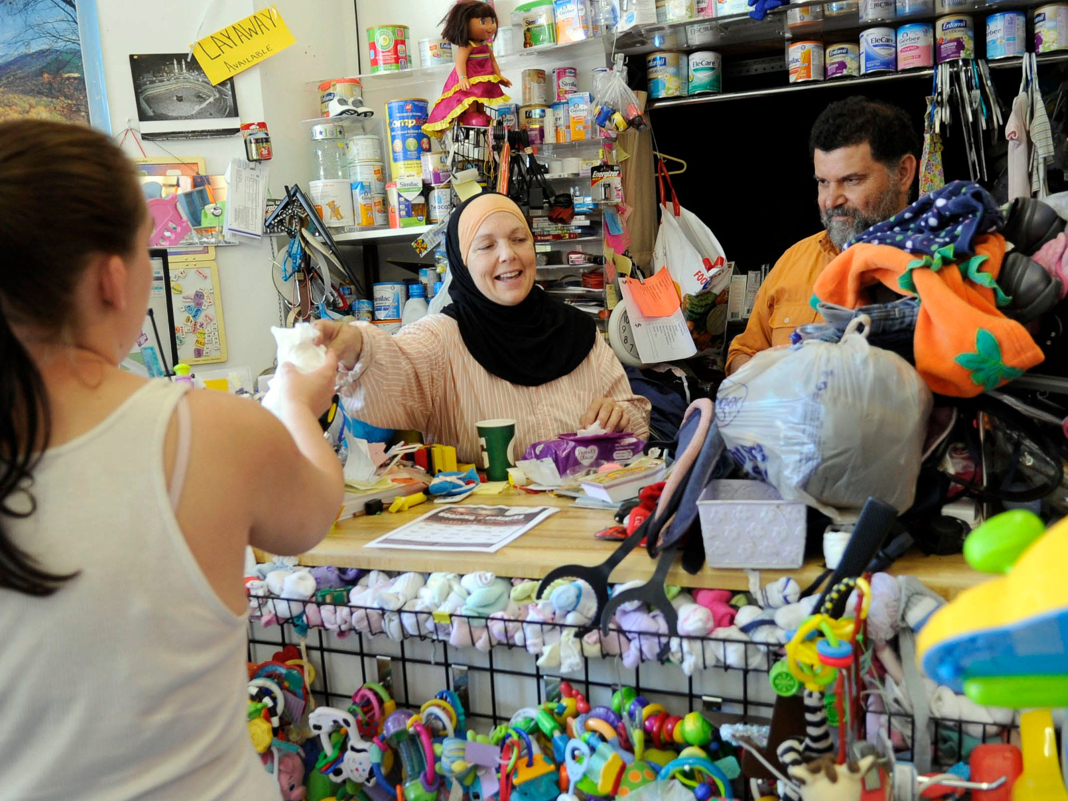 Rebecca and Fathi Husain, owners of Wee Care on Chapman Hwy., help a customer on Wednesday, Aug. 22, 2012. Wee Care is one of twenty south Knoxville businesses taking part in the South Knoxville Booming the Business loyalty card. Entrants must get 15 of the 20 participating businesses to stamp their card, giving them a chance to win $2,500, a VIP pass to Boomsday, and turning on the lights of the newly restored JFG sign.